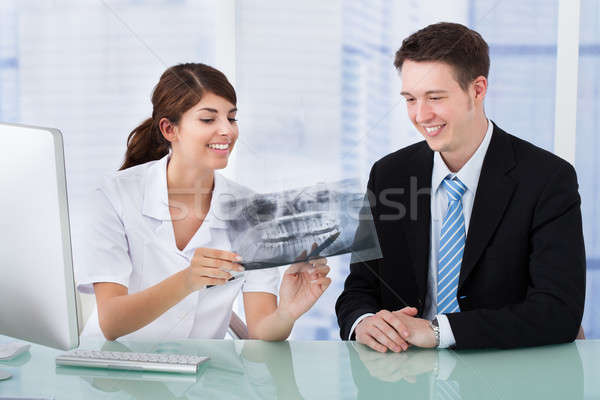 Dentist Showing Jaw Xray To Businessman In Clinic Stock photo © AndreyPopov