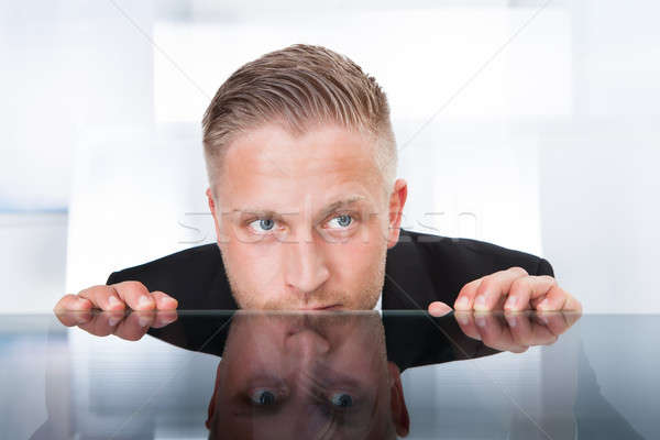 Businessman peering furtively over the top of his desk Stock photo © AndreyPopov