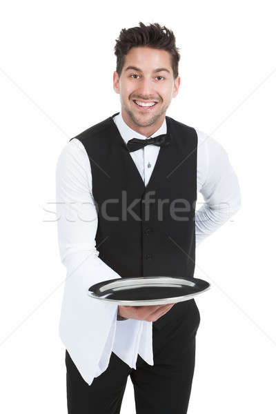 Smiling Young Waiter Holding Empty Serving Tray Stock photo © AndreyPopov