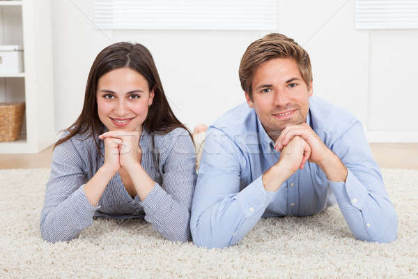 Happy Couple Lying On Rug In Living Room Stock photo © AndreyPopov