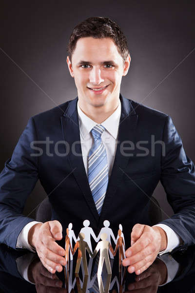 Confident Businessman Protecting Team Of Paper People On Desk Stock photo © AndreyPopov