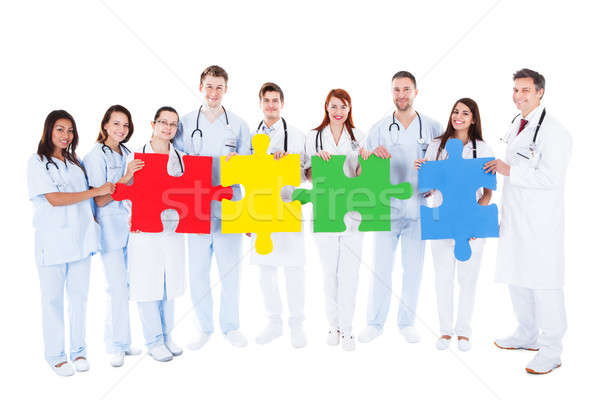 Medical team holding colorful puzzle pieces Stock photo © AndreyPopov