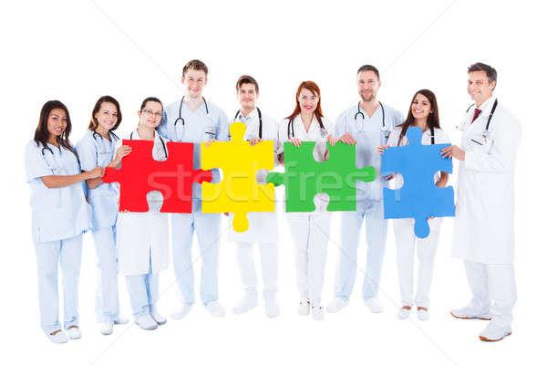Orvosi csapat tart színes kirakó darabok nagyobb csoport Stock fotó © AndreyPopov