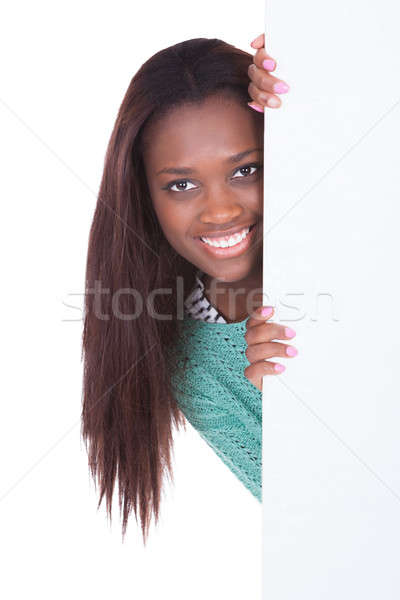 Woman peeping from behind of billboard over white background Stock photo © AndreyPopov
