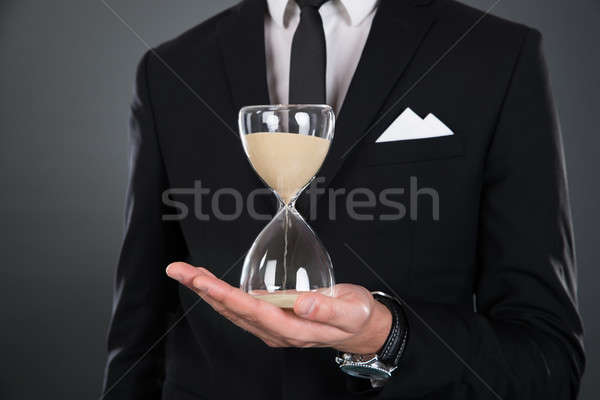 Midsection Of Businessman Holding Hourglass Stock photo © AndreyPopov