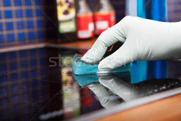 Person's Hand Cleaning Induction Cooker With Scrubber Stock photo © AndreyPopov
