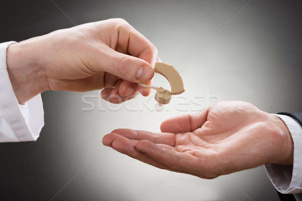 Doctor Giving Hearing Aid To Patient Stock photo © AndreyPopov