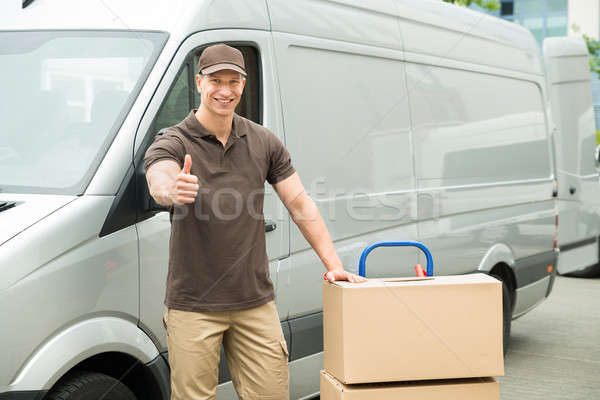 Delivery Man With Cardboard Boxes Showing Thumbs Up Sign Stock photo © AndreyPopov