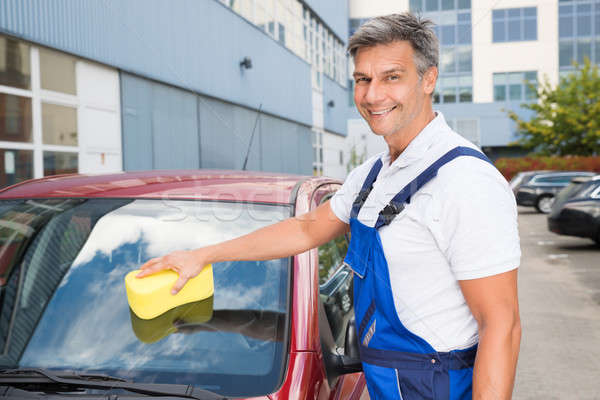 Happy Male Worker Cleaning Car Windshield With Sponge Stock photo © AndreyPopov