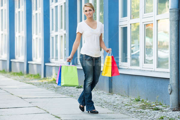 Woman Carrying Shopping Bags On Sidewalk Stock photo © AndreyPopov