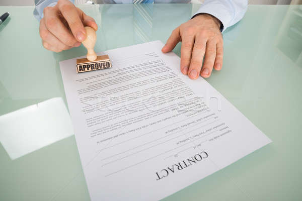 Businessman Stamping On Contract Form Stock photo © AndreyPopov