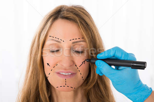 Surgeon Drawing Correction Lines On Woman Face Stock photo © AndreyPopov