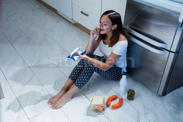 Woman Eating Chocolate In Kitchen Stock photo © AndreyPopov