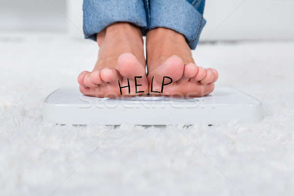 Person On Weighing Scale Showing Help Text Stock photo © AndreyPopov