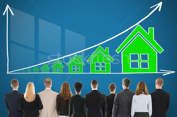 Businesspeople Looking At House Raise Concept On Wall Stock photo © AndreyPopov