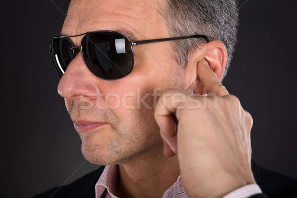 Male Security Guard Listening To Earpiece Stock photo © AndreyPopov
