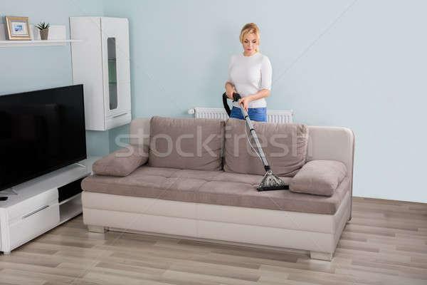Nő takarítás kanapé porszívó fiatal nő otthon Stock fotó © AndreyPopov