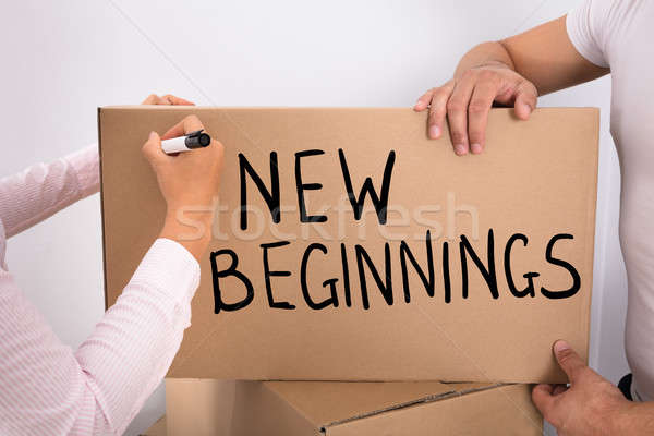 Woman Writing New Beginnings On Box Stock photo © AndreyPopov