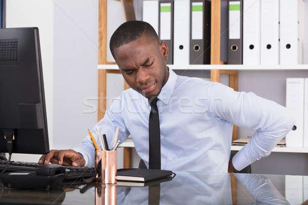 Imprenditore sofferenza mal di schiena giovani african lavoro Foto d'archivio © AndreyPopov