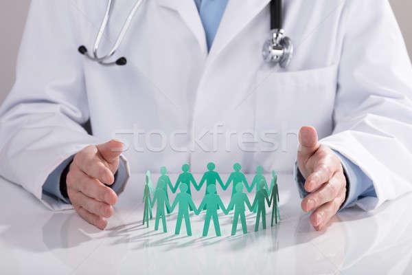 Orvos papír kivágás asztal közelkép orvosok kéz Stock fotó © AndreyPopov