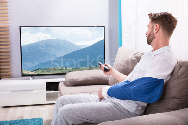 Young Man With Fractured Hand Watching Television At Home Stock photo © AndreyPopov