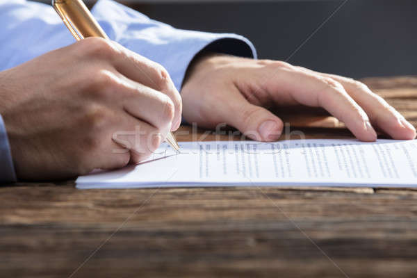 Businessperson's Hand Signing Document Stock photo © AndreyPopov