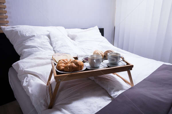 Croissants And Cup Of Tea On Bed Stock photo © AndreyPopov