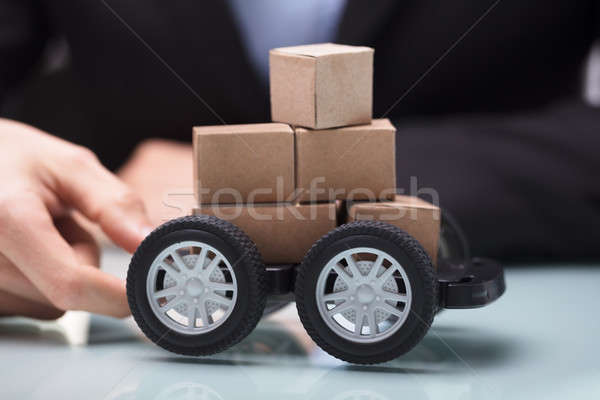 Hand Holding Black Cart With Stack Of Miniature Cardboard Boxes Stock photo © AndreyPopov