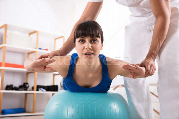 Physiotherapist Assisting Woman While Doing Exercise Stock photo © AndreyPopov