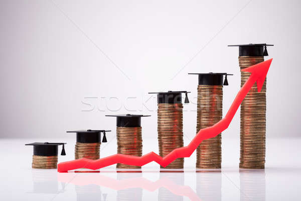 Increasing Red Arrow In Front Of Coins With Graduation Hat Stock photo © AndreyPopov