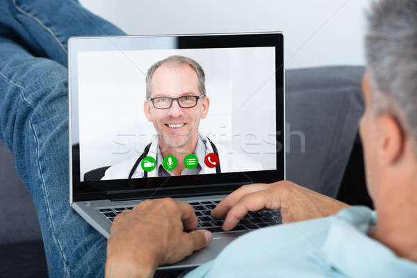 Man Videoconferencing With Doctor On Laptop Stock photo © AndreyPopov