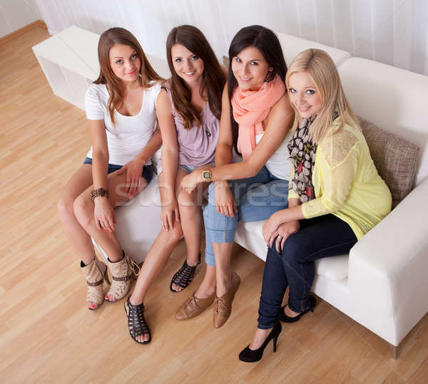 Young ladies sitting on a couch at home Stock photo © AndreyPopov