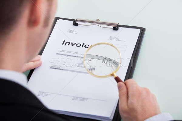 Businessman Examining Invoice Through Magnifying Glass Stock photo © AndreyPopov