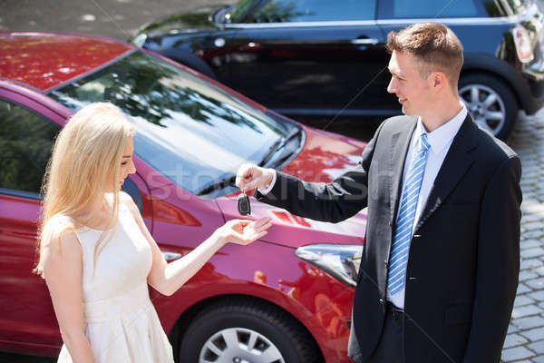 Salesman Handing Key To Woman By New Car Stock photo © AndreyPopov