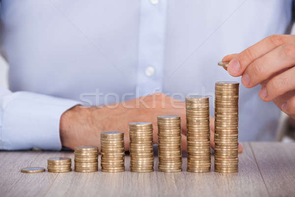 Businessman Stacking Euro Coins At Desk Stock photo © AndreyPopov