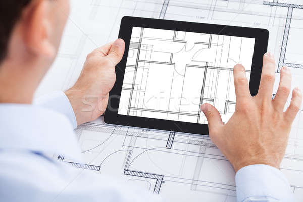 Architect Analyzing Blueprint On Digital Tablet Stock photo © AndreyPopov