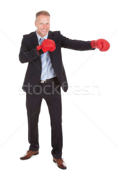 Businessman In Boxing Gloves Punching Over White Background Stock photo © AndreyPopov