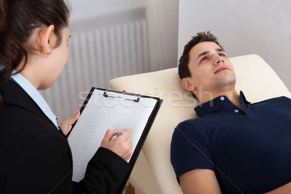 Patient Lying On Bed While Psychologist Writing Notes Stock photo © AndreyPopov