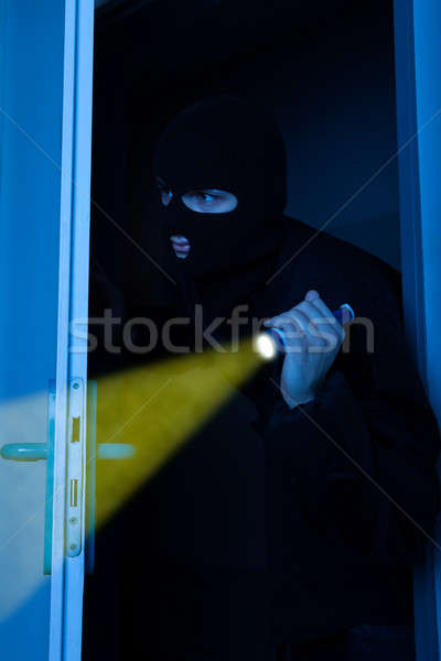Thief Holding Flashlight While Entering Into House Stock photo © AndreyPopov