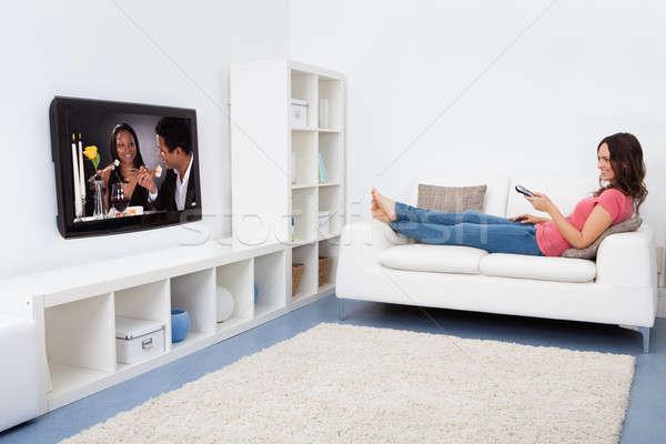 Kobieta oglądanie telewizji portret uśmiechnięta kobieta posiedzenia kanapie Zdjęcia stock © AndreyPopov
