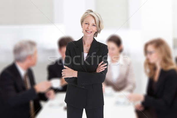Businesswoman Standing With Arms Crossed In Boardroom Stock photo © AndreyPopov