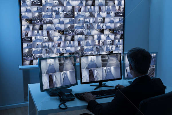 Man In Control Room Monitoring Cctv Footage Stock photo © AndreyPopov