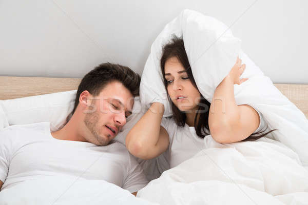Woman Covering Ears While Man Snoring On Bed At Home Stock photo © AndreyPopov