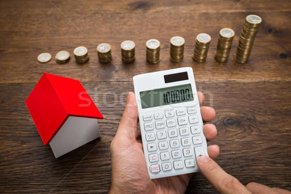 Businessman With Coins And House Model Using Calculator Stock photo © AndreyPopov