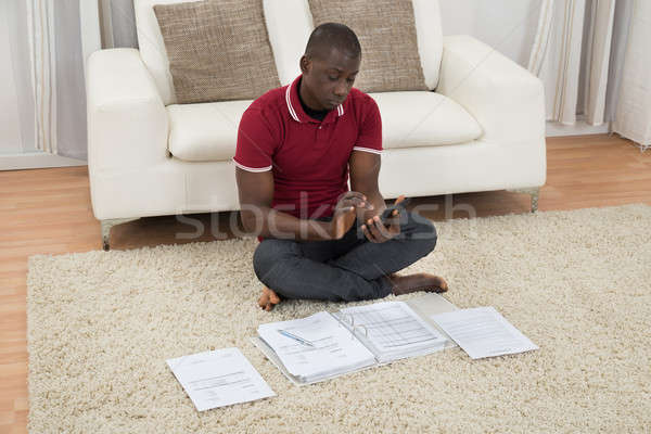 Man Calculating Invoices Using Calculator Stock photo © AndreyPopov
