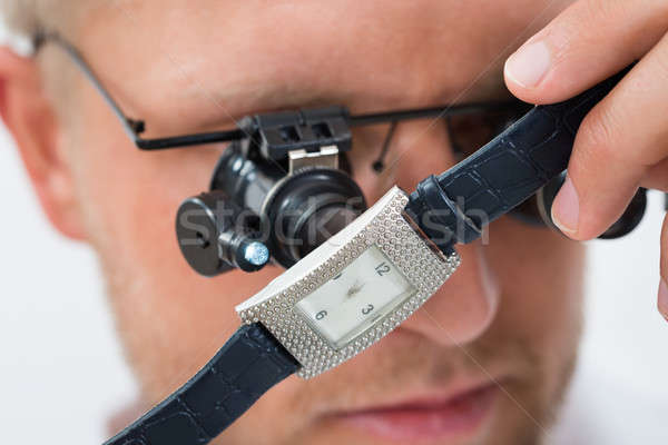 Man Looking Wrist Watch With Loupe Stock photo © AndreyPopov