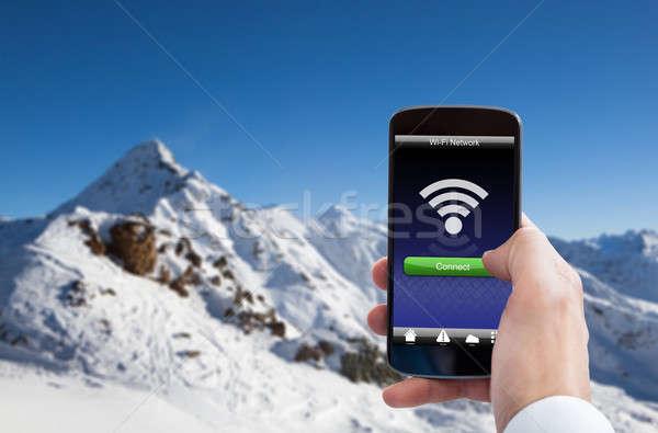 Kéz tart mobiltelefon wifi jel közelkép Stock fotó © AndreyPopov
