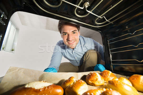 Man Taking Out Bread View From Inside The Oven Stock photo © AndreyPopov
