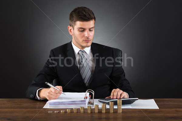 Businessman Calculating Tax With Coins At Desk Stock photo © AndreyPopov