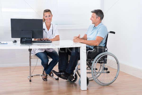 Człowiek posiedzenia wózek konsultacji lekarza uśmiechnięty Zdjęcia stock © AndreyPopov
